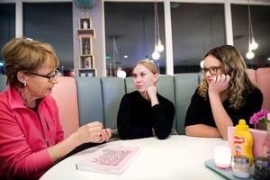Alva Larsson och Clara Lindström häpnar när Mona Johansson berättar om hur mensskydd fungerade på 1960-talet.