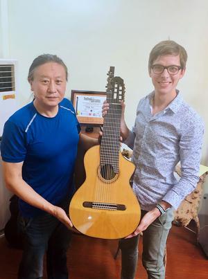 Guo Yulong, en av Kina främsta gitarrtillverkade, och Nils Klöfver håller i den första altgitarren som någonsin tillverkats i Kina.