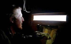 Bengt Nordström håller utkik genom en av de tre gluggar som finns i väggen, medan kameran står redo att avfyra några bildrutor genom en annan öppning i väggen.