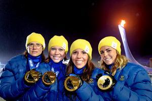 Sveriges Ida Ingemarsdotter, Emma Wikén, Charlotte Kalla och Anna Haag visar upp sina guldmedaljer efter segern i Sotji 2014. Bild: Joel Marklund/Bildbyrån.