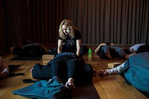 Instruktören Lotta Renlund börjar yogaklassen och alla deltagare följer vant hennes ord. Hon går fram och lägger handen på deras axlar för att hjälpa till med avslappningen.