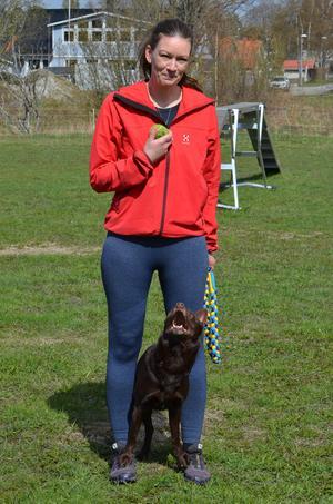 Caroline håller i Liljas älskade tennisboll. Lilja gör vad som helst för bollen.