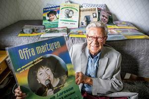 Fritz Hultgren med affisch på Babben Larsson och alla de andra kändisarna han arrangerat föreläsningar med.