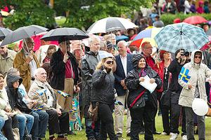 Vädret skiftade. Besökarna fick packa ner de små flaggorna och fälla upp paraplyerna, de som hade ett med sig.