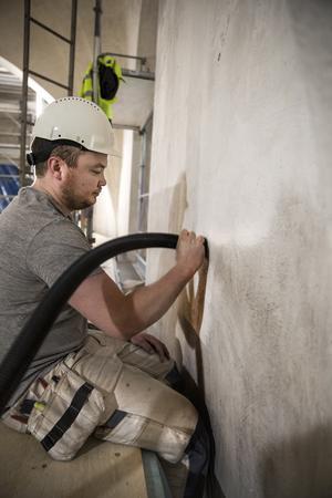 Joakim Persson sitter på byggställningen och arbetar med att rugga ytan och dammsuga rent väggarna och taket i kyrkan.