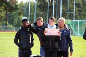 Adam och Daniel Hansson med checken till Parasportförbundet Dalarna. Med på bilden Maslah Omar i bakgrunden och Ola Brossberg.