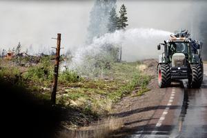 En traktor hjälper till med släckningsarbetet i det branddrabbade området runt Färila. Foto: Erik Simander / TT