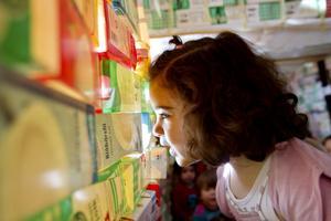 """Kul att leka i. Therese och Melvin Forsberg leker gärna i Stadshuset som barnen på Brukets förskola byggt av nästan 1 000 urdruckna mjölkkartonger. """"Det tog flera veckor att bygga"""", berättar femåriga Melvin.Tittut. Pela Bekir tittar ut genom ett av fönstren i Stadshuset i mjölkkartong."""