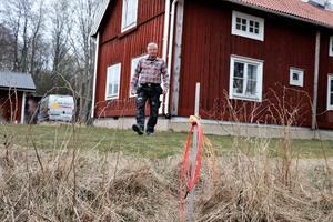 Olli stegar sex meter  från husfasaden till fiberslangen som ligger redo att kopplas in.