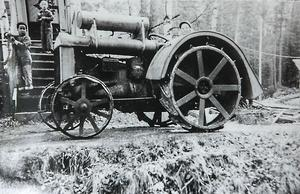 På gården fanns även en ångdriven traktor med järnhjul. Här på bilden kan man se Gösta längst upp på trappen framför honom står Jörgen Thander och på traktorn sitter hans syster Barbro Ekström.