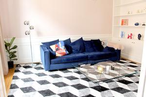 Djup soffa och grafiskt mönstrad matta för skönt soffmys i TV-rummet.