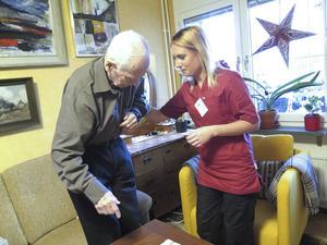 Alexandra Jansson hjälper Olle Widqvist att resa sig ur soffan. Han får besök fyra gånger om dagen av hemtjänstföretaget Maid.