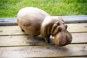 En tjock flodhäst i trä vaktar verandan.