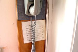 Gammal väggtelefon med viktiga nummer.