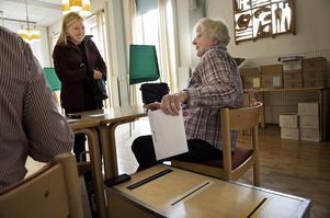 Maria Skansebo från Kungälv, som studerar i Falun, förtidsröstar på Kristinegården. Hennes röstsedlar tas om hand av förtidsröstmottagaren Karin Michols. Foto:Stina Rapp
