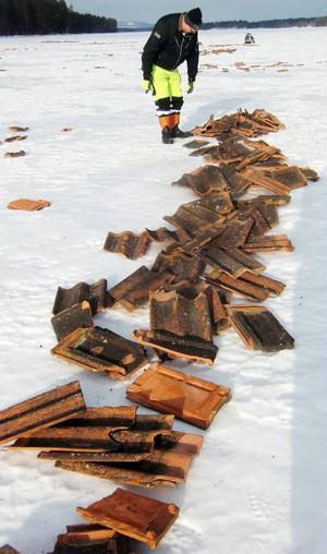Gunnar Persson i Näversjöberg, i Krokoms kommun, inspekterar mängden kasserade tegelpannor som oväntat lagts ut på sjön som ligger nedanför byn.