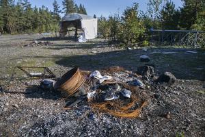 I en eldstad utanför ett tält ligger resterna av ett gammalt hjul.