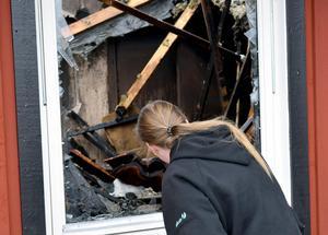 Petra och tittar in genom ett fönster där värmen från branden tryckt sönder glaset.