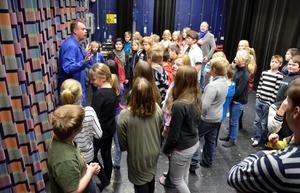 Schhh... Rune Jakobsson tyster ner femteklassarna där de väntar på att ridån ska gå upp. Snart ska de få känna på hur det är att stå på en teaterscen.