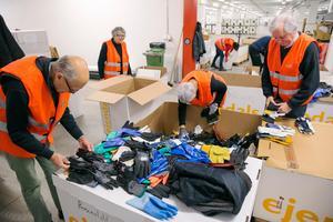 Skänkta handskar och skor sorteras och läggs i lådor av frivilliga.