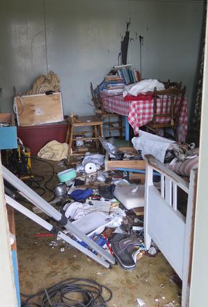 Knappt en hel sak finns kvar i stugan. Stolarna är sönderslagna, färg på väggen, porslin, husgeråd, allt är kastat med kraft i golvet eller ut genom de krossade fönstren.