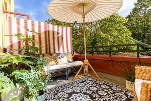 En rymlig balkong på Staketgatan som Therese möblerat med ett parasoll, rottingmöbler och gröna växter. Foto: Alexander Lindström
