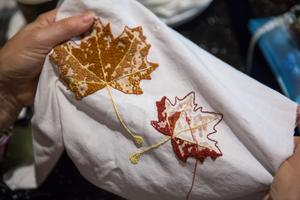 Sommarens tema för broderiklubben är löv och Monica Öhman använder sig av en fransk knut-teknik för att få till sina.