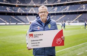 Herrlandslagets förbundskapten Janne Andersson poserar med checken som Gräsroten delar ut till ungdomsidrotten i Dalarna. Foto: Bildbyrån