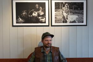 Kristofer Hallberg framför två av sina foton från Lillhärjåbygget: Eva kärnar smör och Kenneth med kalv.