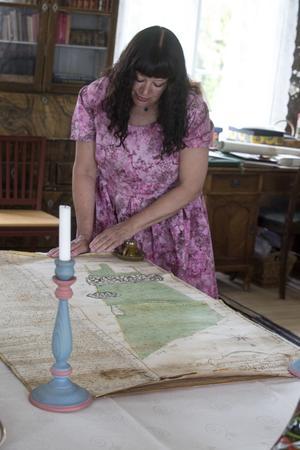 Karin rullar försiktigt ut den äldsta skogsinventeringskartan, från 1749, på ett av matborden. Den är handgjord och vacker som en tavla.