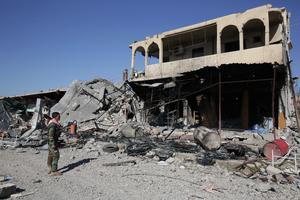 En peshmergasoldat står vid ett utbombat hus i staden Sinjar. Foto: Bram Janssen/TT