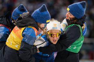 En utmattad Stina Nilsson bärs upp av sina lagkamrater efter sistasträckan. Bild: Joel Marklund/Bildbyrån.