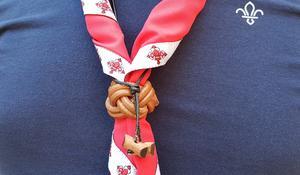 Det var när scoutrörelsen grundades i början av 1900-talet som upphovsmannen Robert Baden Powell ville ha en enhetlig dräkt som skapar gemenskap och som inte visar personens samhällsklass. Det finns olika varianter av scoutdräkter, men i grunden bär man en skjorta, pikétröja eller som här en t-shirt samt scouthalsduk som spänns fast med en sölja eller ett spänne. Och så har man på sig olika märken man har fått och som berättar vad man har gjort, tillhörighet och annat. Förutom halsduken med söljan bär Samer Aso också Wood Badge-pärlorna som scoutledare när de slutför en viss utbildning. Pärlorna representerar ledarskap och mod och användes redan vid den första ledarskapsutbildning i september 1919 i Gilwell Park.