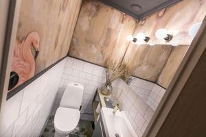 Toaletten i huset är målad för att se fuktskadad ut. Flamingon är en del av den tidigare tapeten.