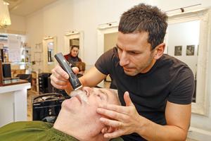 Innan det är dags för rakningen trimmar barberaren Emanuel Özel Hans Karlsson mustasch.