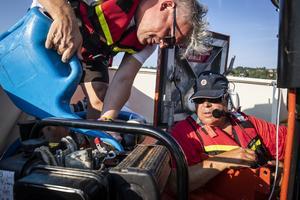 Roland Nilsson och Christer Hörnfeldt gör i ordning pumpen för att pumpa ur vatten från den finska båten.