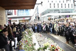 Blommor vid Åhléns på Drottninggatan i Stockholm i samband med en tyst minut efter terrorattentatet. Foto: Noella Johansson / TT