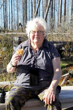 Solveig Wadelius njuter i solen vid Björntjärnen. När du besöker Hälleskogsbrännan kom ihåg att ta med fika och gärna något att grilla. Det finns gott om grillplatser i området.