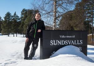 Stefan Johansson står vid Välkommen till Sundsvall-skylten. Att det står golfklubb där syns inte för all snö.