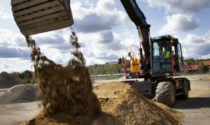 Kommunalrådet Mikael Löthstam (S) gräver en första symbolisk skopa för det påbörjade arbetet med infrastrukturen på Kattvikskajen.