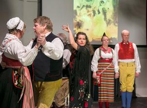 Karin Jalvén omringas av folkdansare på scenen i Tingshuset.