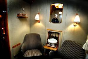 Här ska kungaparet sitta. Järnvägsmuseets chef Robert Sjöö visar upp salongen i kungavagnen där kungen och drottningen kommer att sitta under tågresan från Furuvik in till Gävle. Salongen liksom resten av vagnen är inredd i stram 50-talsstil. I grågrönt med böljande trä och ljusa läderdetaljer.