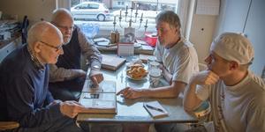 Storebror Henning Sjöman, närmast till vänster, bläddrar i ett av fotoalbumen som plockats fram i köket på Bivur. Ivars tvillingbror Sven tittar på, liksom sönerna Pelle och Jim till höger.