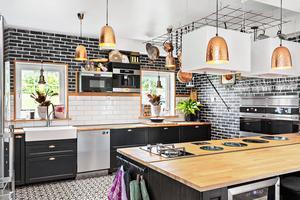 Kök i öppen planlösning med bland annat två kylar och frysar, dubbla vinkylar, gasspis och diskmaskin.  Foto: PAX Fastighetsmäklare/Stefan Strindberg
