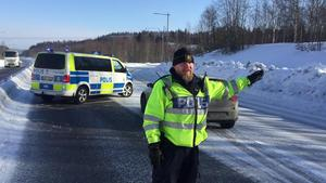 Polismannen Niklas Modig leder om trafiken några mil ifrån olyckan.