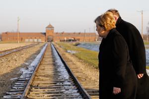 Tysklands förbundskansler Angela Merkel vid järnvägsspåren som leder till koncentrationslägret Auschwitz-Birkenau. Foto: Markus Schreiber/AP Photo