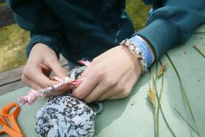 Matilda Andersson gör armband med hjälp av gamla mattrasor och ståltråd.