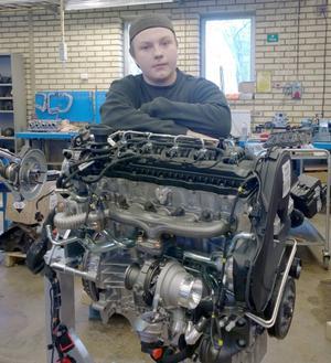 Henrik Rantakallio poserar i skolan med en motor.