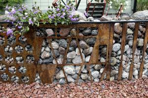 Muren av plåtskrot, armeringsjärn och sten är ett smycke i P-G:s och Helenas stenträdgård.