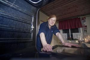 Mats Olsson tittar in i sin trasiga ugn. En ny lucka kan han få genom försäkringsbolaget, men självrisken är dyrare än vad en ny lucka kostar.